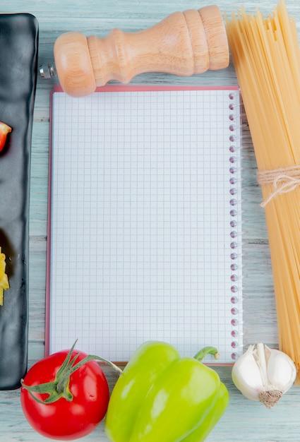 コピースペース付きの木製テーブルの春雨ペッパーガーリックトマトとメモ帳の側面図 無料写真