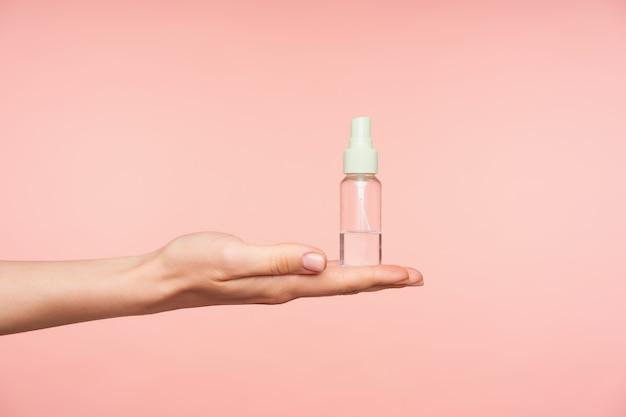 ピンクの背景に対して分離された、液体の透明なスプレーボトルを保持しながら手のひらを上に保つ手入れの行き届いた女性の手の側面図 無料写真