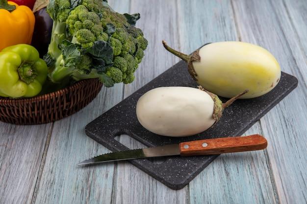 Вид сбоку белых баклажанов с ножом на разделочной доске и перцем брокколи в корзине на деревянном фоне Бесплатные Фотографии