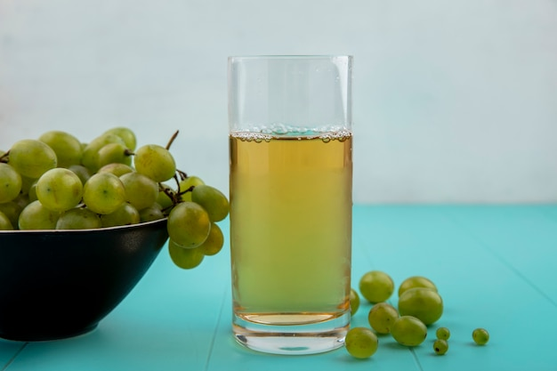 ガラスの白ブドウジュースと青い表面と白い背景の上のブドウの果実とブドウのボウルの側面図 無料写真