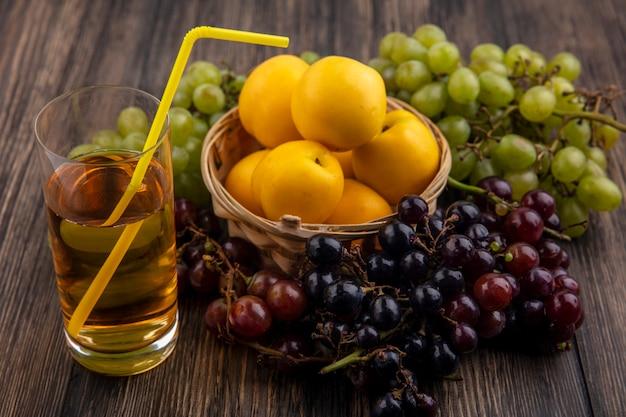 木製の背景にブドウとバスケットのネクタコットとして果物とガラスの白ブドウジュースの側面図 無料写真