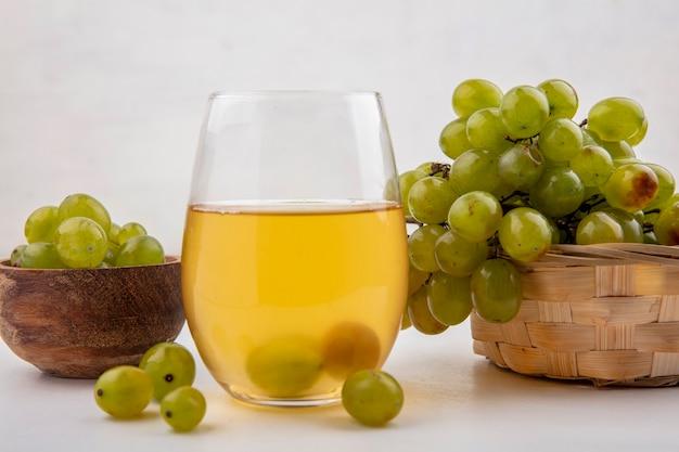 ボウルと白い背景の上のバスケットに白ブドウとガラスの白ブドウジュースの側面図 無料写真