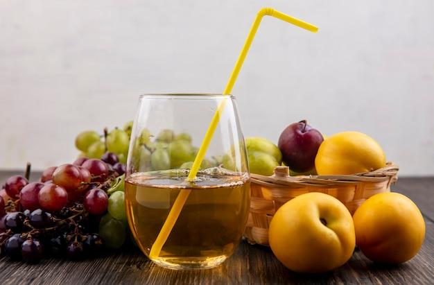 Вид сбоку белого виноградного сока с питьевой трубкой в стекле и фруктов в виде плюотов нектакотов в корзине с виноградом на деревянной поверхности и белом фоне Бесплатные Фотографии