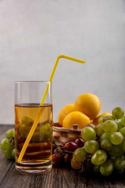 木製の背景にブドウとバスケットのネクタコットとして果物と白ブドウジュースの側面図 無料写真