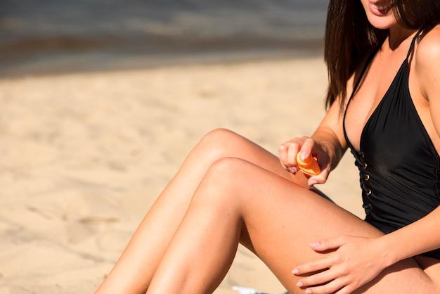 コピースペースとビーチで日焼け止めを適用する女性の側面図 無料写真