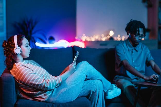 タブレットとヘッドフォンを使用して彼氏と一緒に家で女性の側面図 無料写真