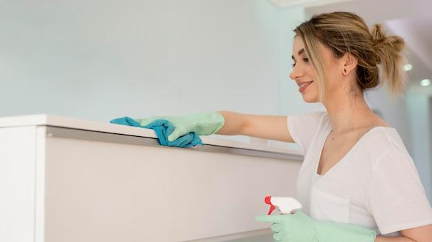 Вид сбоку поверхности чистки женщины с тканью Бесплатные Фотографии