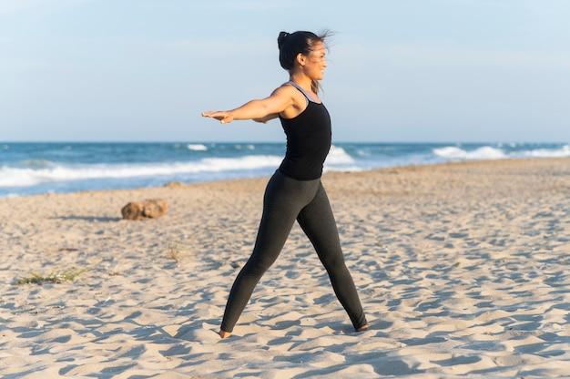 Вид сбоку женщины, занимающейся фитнесом на пляже Бесплатные Фотографии