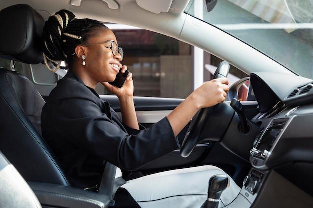 Вид сбоку на женщину, ведущую машину и одновременно разговаривающую по смартфону Бесплатные Фотографии
