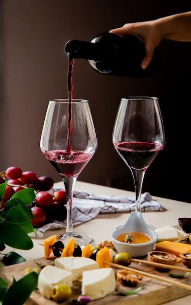 白い表面と黒の背景にグラスと異なる種類のチーズオリーブクルミブドウに赤ワインを注ぐ女性手の側面図 無料写真