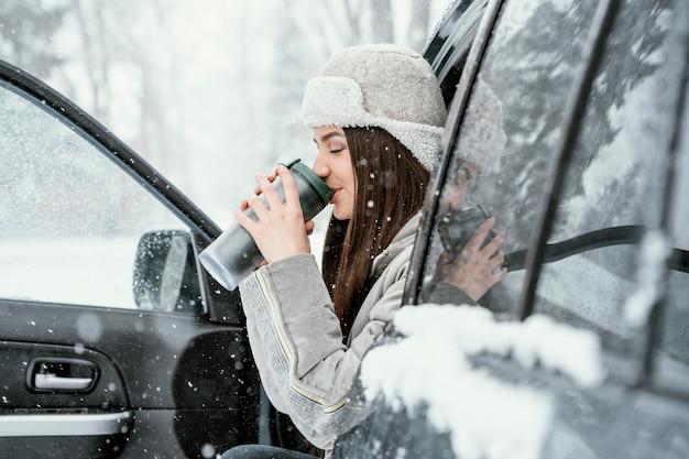 Вид сбоку на женщину с теплым напитком и наслаждение снегом во время поездки Бесплатные Фотографии