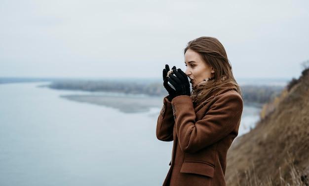 Вид сбоку женщины, пьющей горячий напиток на берегу озера Бесплатные Фотографии