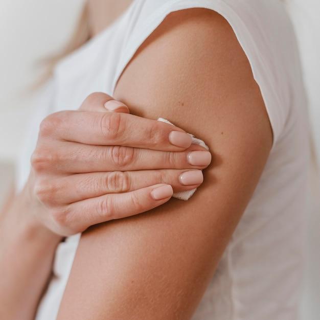 彼女のワクチンを取得した後、彼女の腕を保持している女性の側面図 無料写真