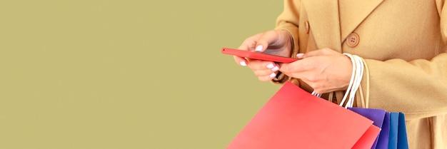 복사 공간 사이버 월요일 스마트 폰 및 쇼핑백을 들고 여자의 측면보기 프리미엄 사진