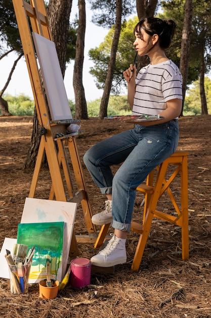 屋外で絵を描く女性の側面図 無料写真