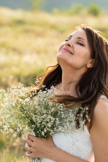 花と自然の中でポーズをとる女性の側面図 無料写真
