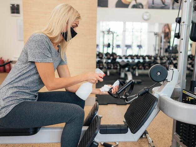 ジム設備に消毒剤をスプレーする女性の側面図 無料写真