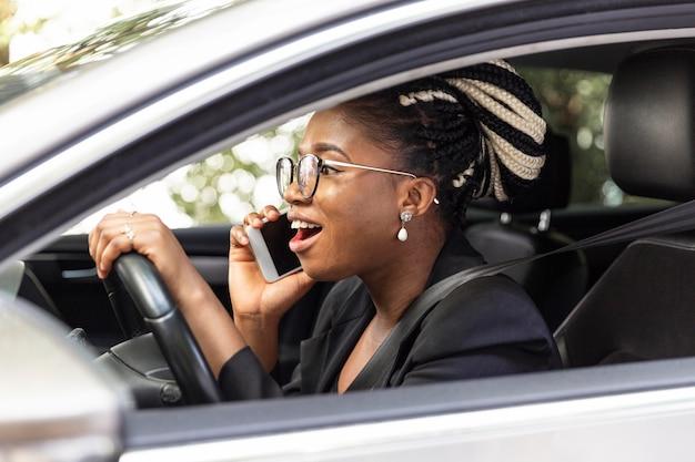 彼女の車を運転している間スマートフォンで話している女性の側面図 無料写真