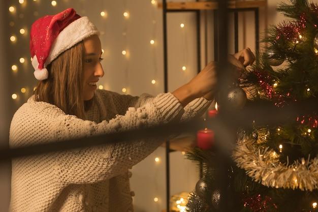 Вид сбоку женщины через окно, украшающей елку Бесплатные Фотографии