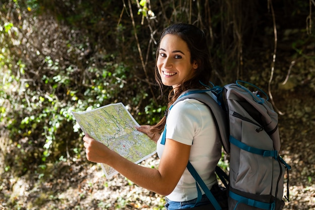 地図を使用しながら自然を探索しようとしている女性の側面図 無料写真