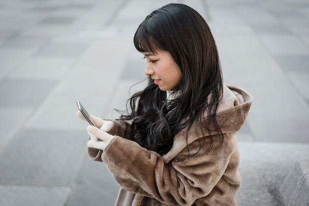 Вид сбоку женщины, использующей смартфон на открытом воздухе Premium Фотографии