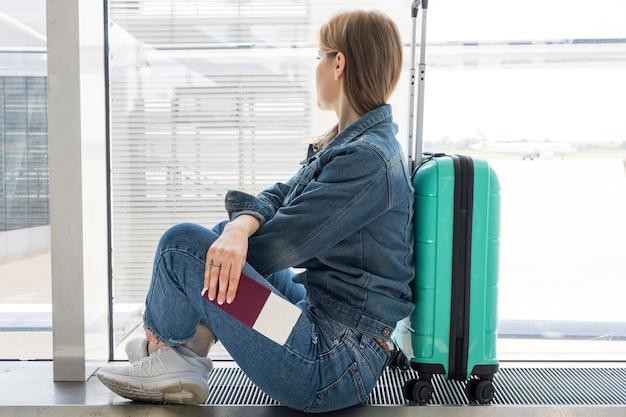 Вид сбоку женщина ждет в аэропорту Бесплатные Фотографии