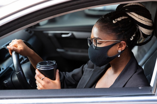 Вид сбоку женщины с маской для лица с кофе в ее машине Premium Фотографии