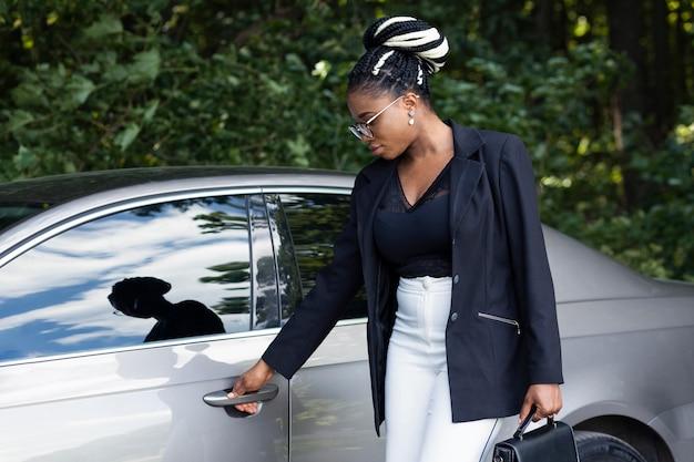 Вид сбоку женщины с сумочкой, открывающей дверцу машины Premium Фотографии