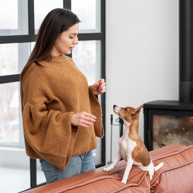 Вид сбоку женщины с ее собакой на диване Бесплатные Фотографии