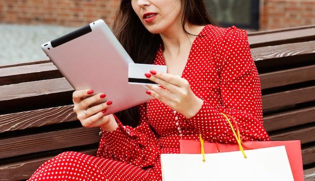 노트북 및 온라인 구매 신용 카드를 가진 여자의 측면보기 무료 사진