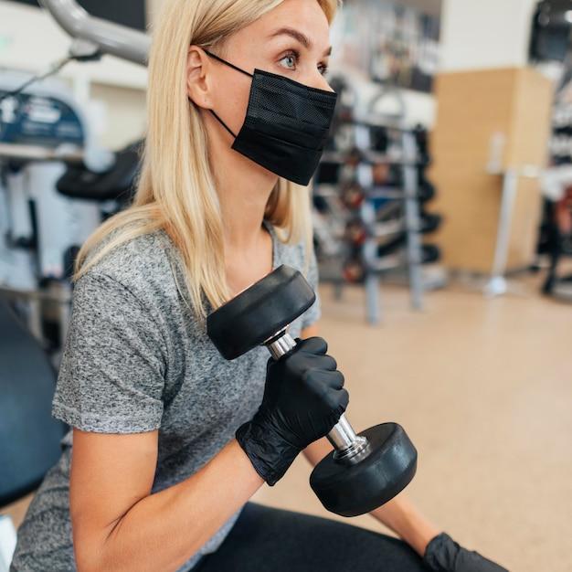 ジムでトレーニングしている医療マスクと手袋を持つ女性の側面図 Premium写真
