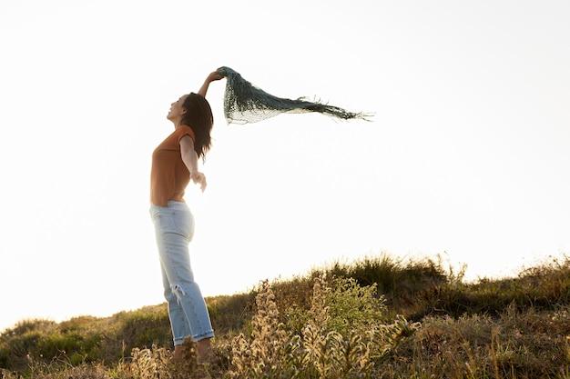 Вид сбоку женщины с шарфом на открытом воздухе Бесплатные Фотографии