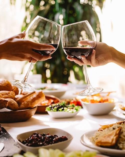 レストランで赤ワインのグラスで乾杯する女性の側面図 無料写真