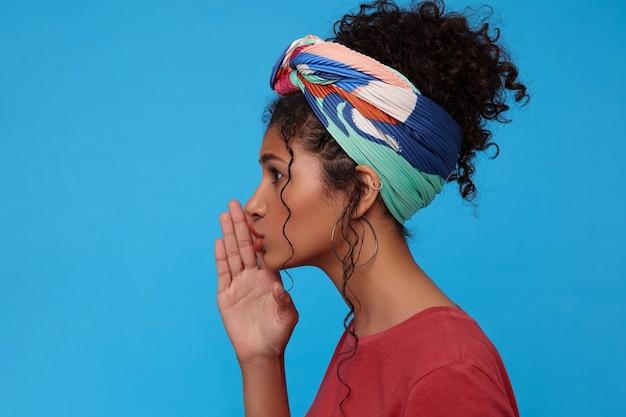 青い壁に隔離された秘密の何かを話している間、彼女の口の近くに上げられた手のひらを保ちながら集められた髪を持つ若い魅力的な黒髪の巻き毛の女性の側面図 無料写真