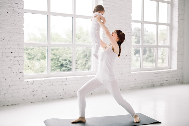 흰 벽과 큰 창문 배경 위에 그녀의 아기와 함께 젊은 어머니 운동의 측면보기. 어머니는 재미와 그녀의 아기와 함께 연주. 프리미엄 사진