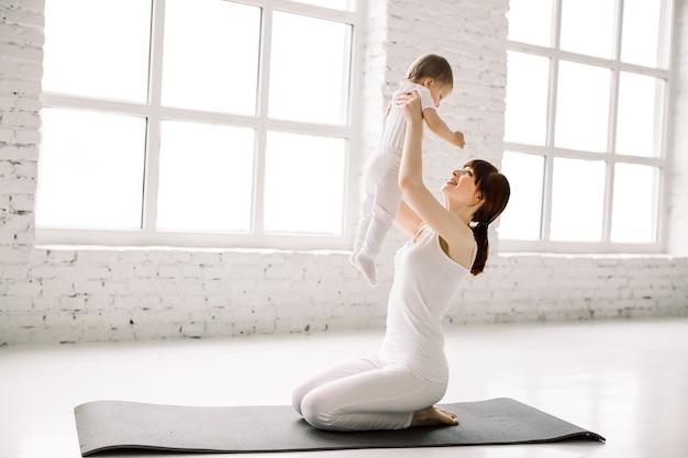 큰 라이트 룸에서 검은 매트에 앉아 그녀의 아기와 함께 젊은 어머니 운동의 측면보기. 어머니는 재미와 그녀의 어린 소녀와 놀고 프리미엄 사진