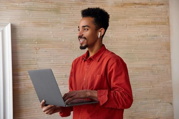 젊은 짧은 머리 어두운 피부 갈색 머리 남자의 측면보기 제기 손에 노트북을 유지하고 베이지 색 인테리어에 서 매력적인 미소로 제쳐두고 찾고 무료 사진