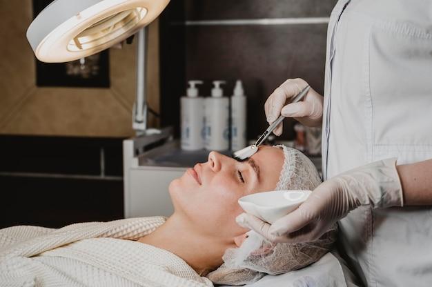 Вид сбоку молодой женщины, получающей лечение кожи лица в спа-салоне Бесплатные Фотографии