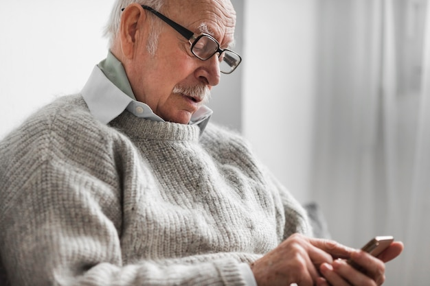 Vista laterale del vecchio in una casa di cura tramite smartphone Foto Gratuite