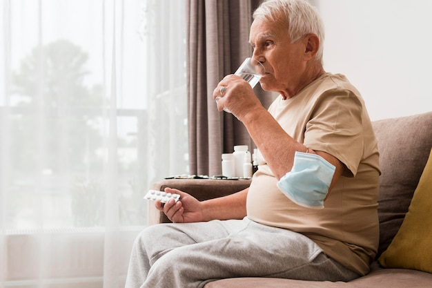 Side view old man taking pill Free Photo