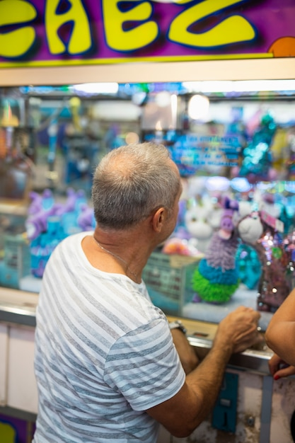 Side view old man at toy stand Free Photo
