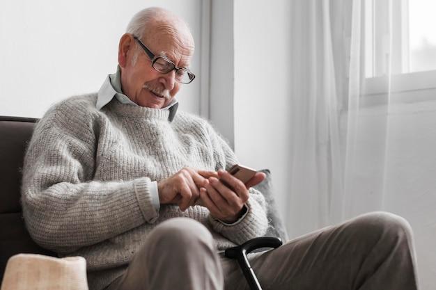 Vista laterale dell'uomo più anziano in una casa di cura tramite smartphone Foto Gratuite