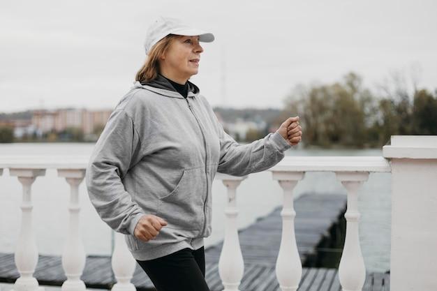 Vista laterale della donna anziana fare jogging all'aperto Foto Gratuite