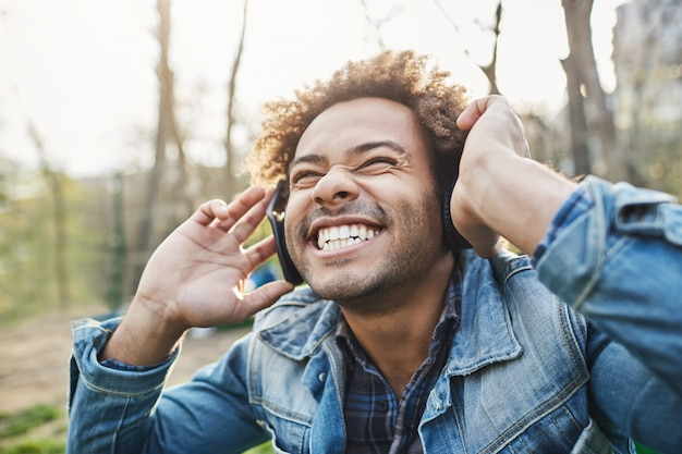 Side-view outdoor portrait of excited happy african man with afro hairstyle holding headphones while listening to music and smiling broadly, being amazed with what he hears. Free Photo