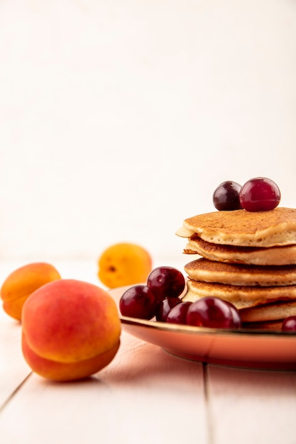 Side view of pancakes with cherries in plate and apricot on wooden surface and white background Free Photo