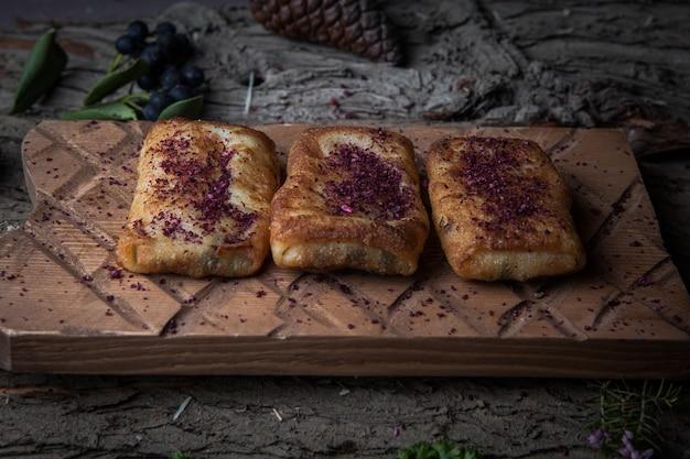 水平木の樹皮の木製スタンドに自家製の肉とサイドビューのパンケーキ 無料写真