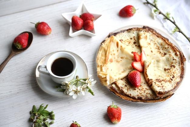 イチゴとコーヒーのカップとサイドビューのパンケーキ 無料写真