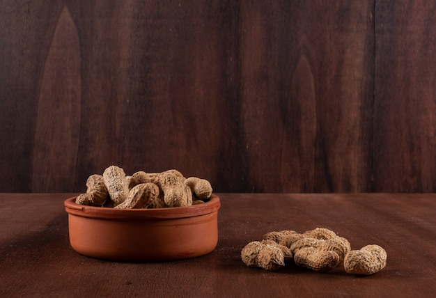 Side view peanuts in bowl on horizontal Free Photo