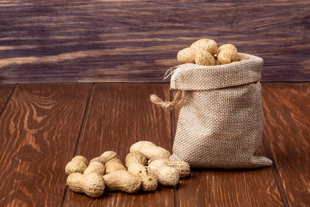 Вид сбоку арахис в скорлупе в сумке и на деревянном столе Бесплатные Фотографии