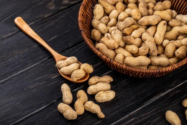 Вид сбоку арахис в скорлупе в корзине и в деревянной ложке на черном деревянном столе Бесплатные Фотографии